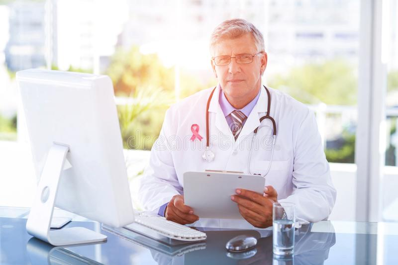 Composite image of portrait of confident male doctor sitting at computer desk royalty free stock image