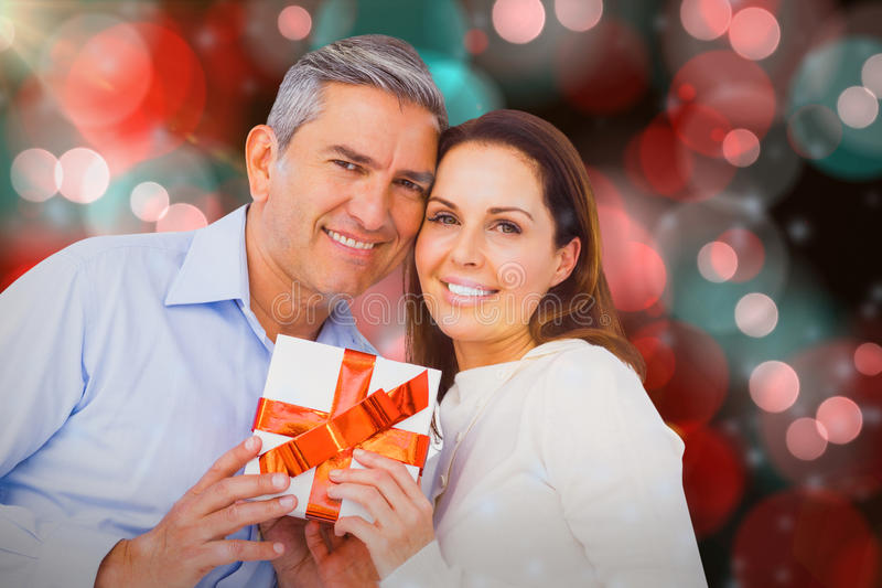Composite image of portrait of couple holding gift. Portrait of couple holding gift against digitally generated twinkling light design royalty free stock photos