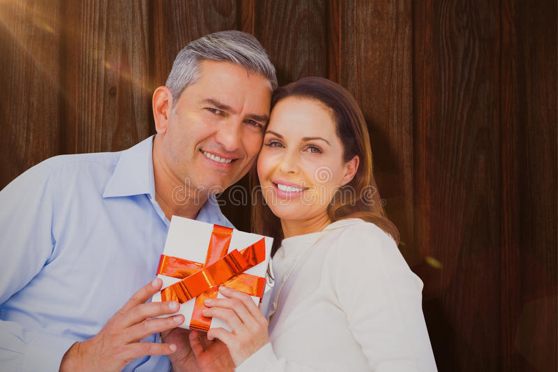 Composite image of portrait of couple holding gift. Portrait of couple holding gift against wood stock photo