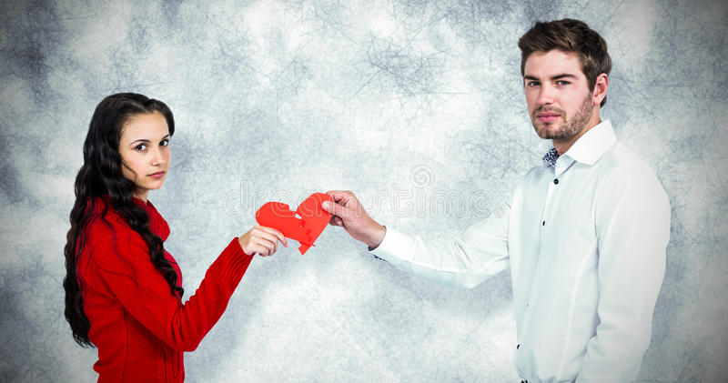 Composite image of portrait of couple holding red cracked heart shape stock photo
