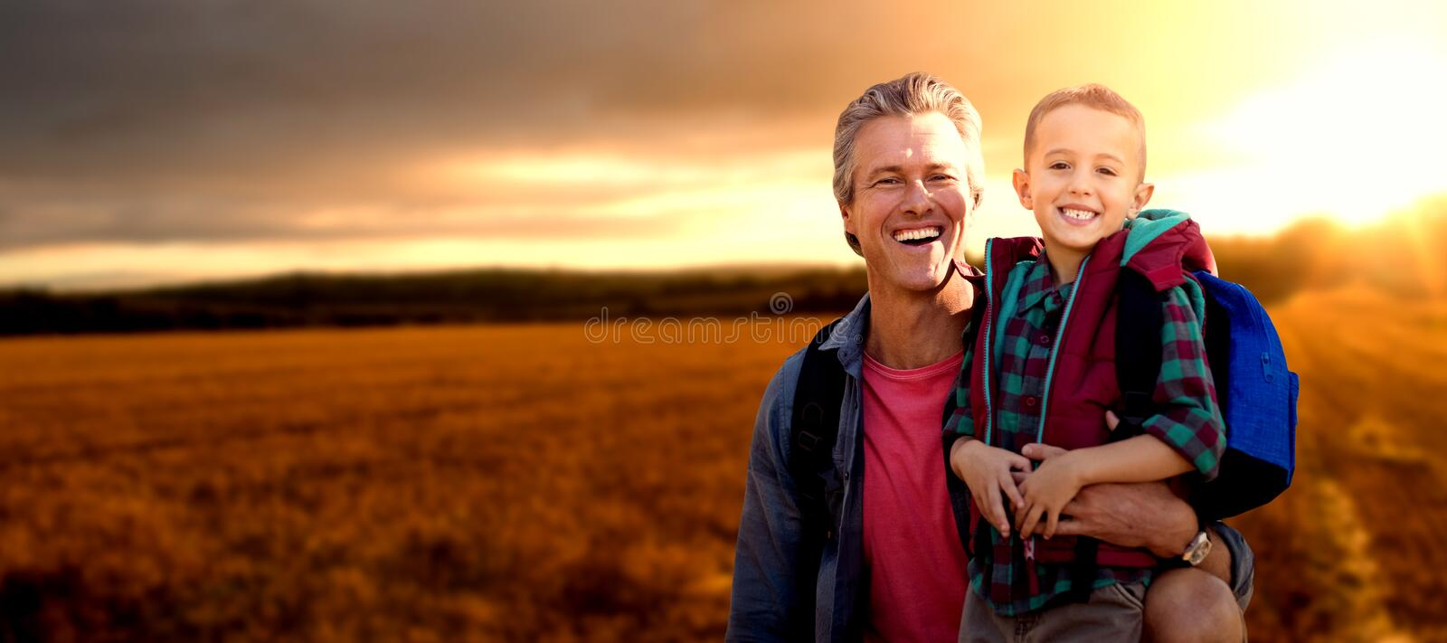 Composite image of portrait of a crouching father beside son stock images