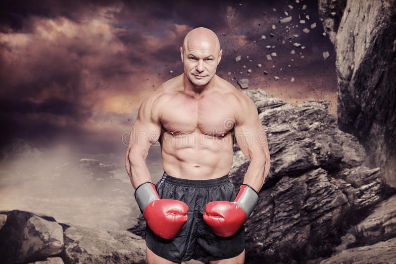 Composite image of portrait full length of bald boxer flexing muscles. Portrait full length of bald boxer flexing muscles against rock crashing down from cliff stock images