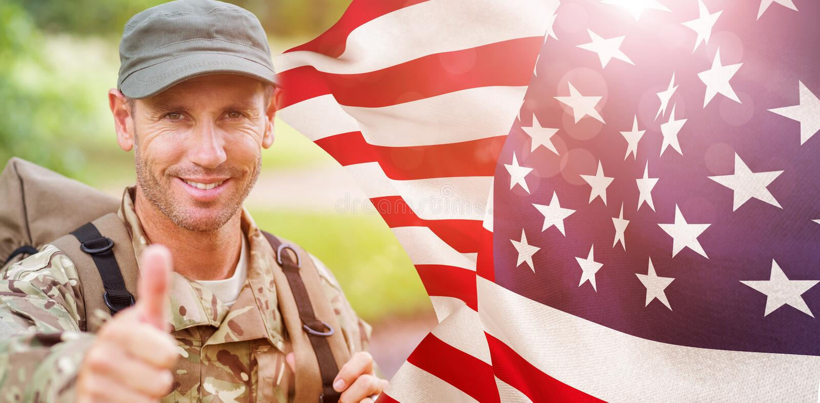 Composite image of portrait of happy army man with thumbs up. Portrait of happy army man with thumbs up against focus on usa flag stock photography