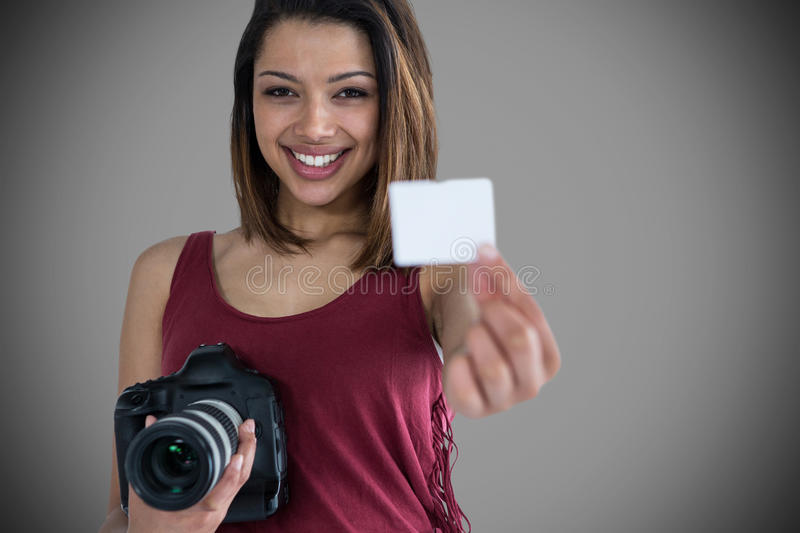 Composite image of portrait of happy woman showing identity card while holding camera royalty free stock photo