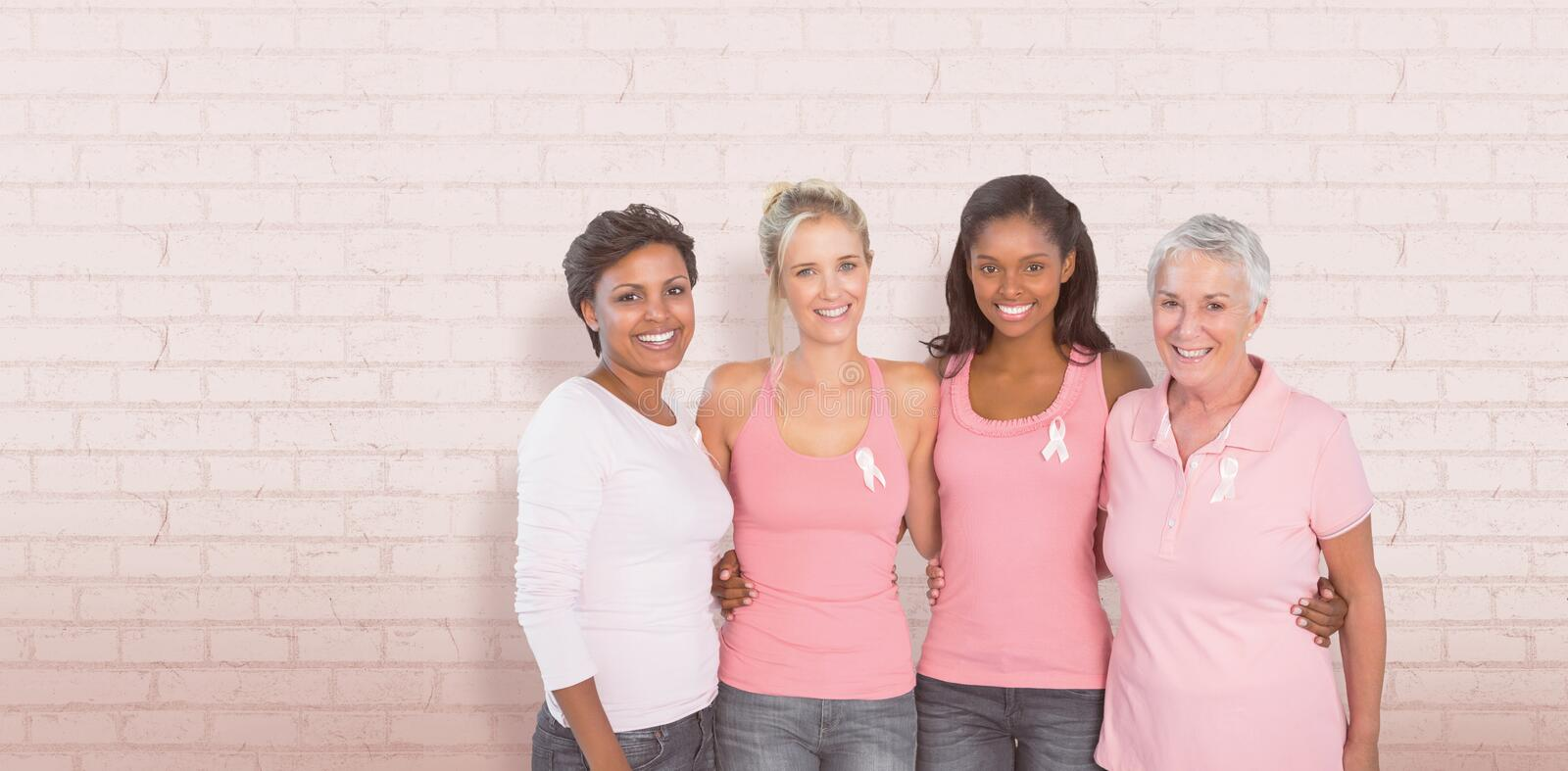 Composite image of portrait of happy women supporting breast cancer social issue. Portrait of happy women supporting breast cancer social issue against white royalty free stock image