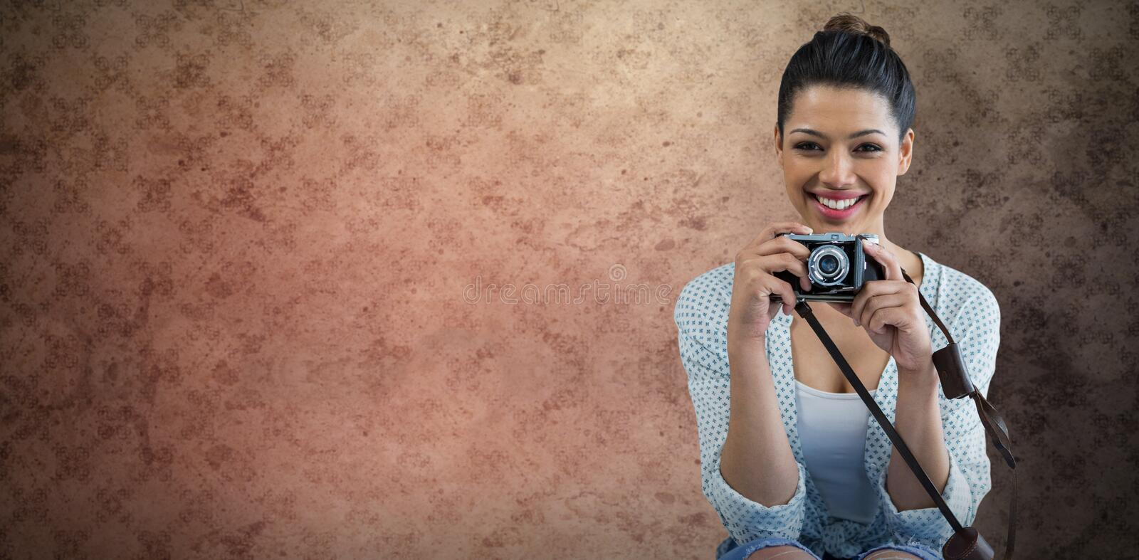 Composite image of portrait of happy young woman holding camera stock images