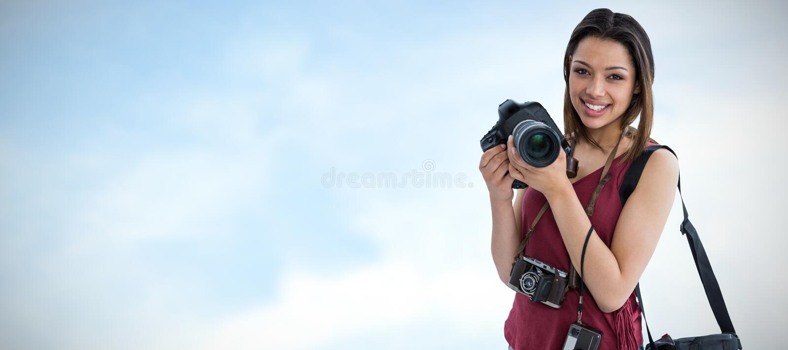 Composite image of portrait of happy young woman holding digital camera stock photography