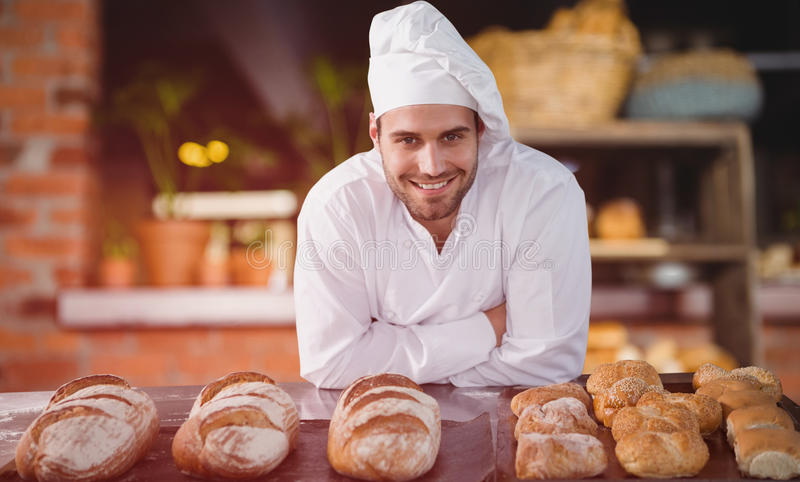 Composite image of portrait of male chef standing by bread at table. Portrait of male chef standing by bread at table against empty counter at coffee shop royalty free stock photography