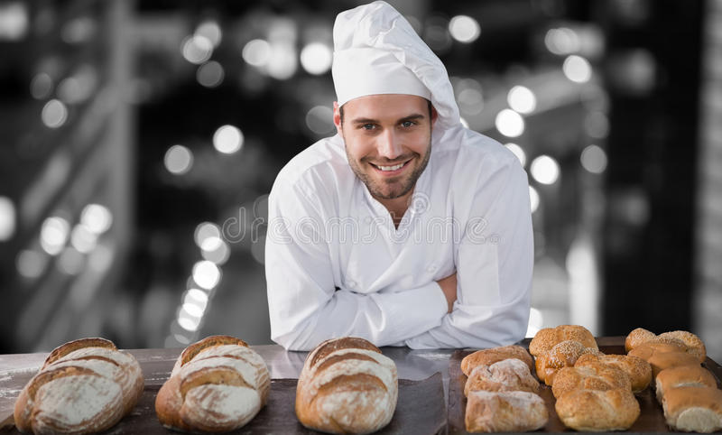 Composite image of portrait of male chef standing by bread at table. Portrait of male chef standing by bread at table against glowing road in city at night royalty free stock image
