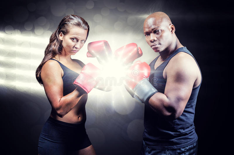 Composite image of portrait of male and female athletes with fighting stance royalty free stock photography