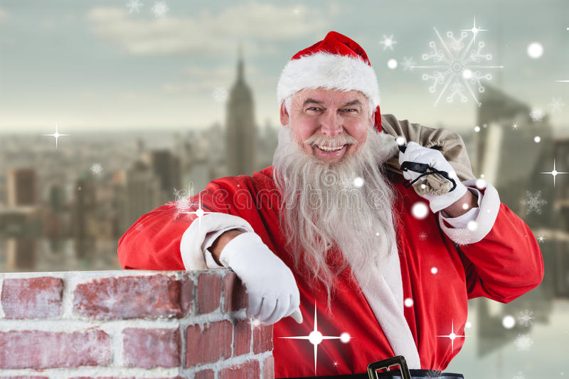 Composite image of portrait of santa claus carrying bag full of gifts royalty free stock image
