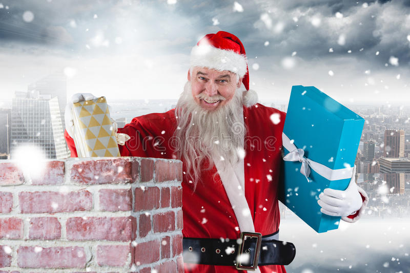 Composite image of portrait of santa claus placing gift boxes into chimney stock photo