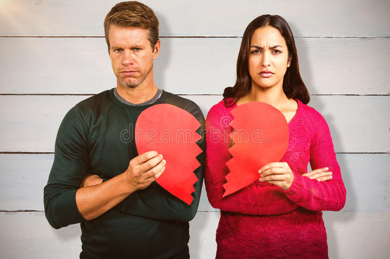 Composite image of portrait of serious couple holding cracked heart shape. Portrait of serious couple holding cracked heart shape against painted blue wooden stock image