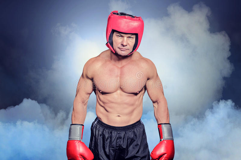 Composite image of portrait of shirtless man with boxing headgear and gloves. Portrait of shirtless man with boxing headgear and gloves against cloudy sky royalty free stock image