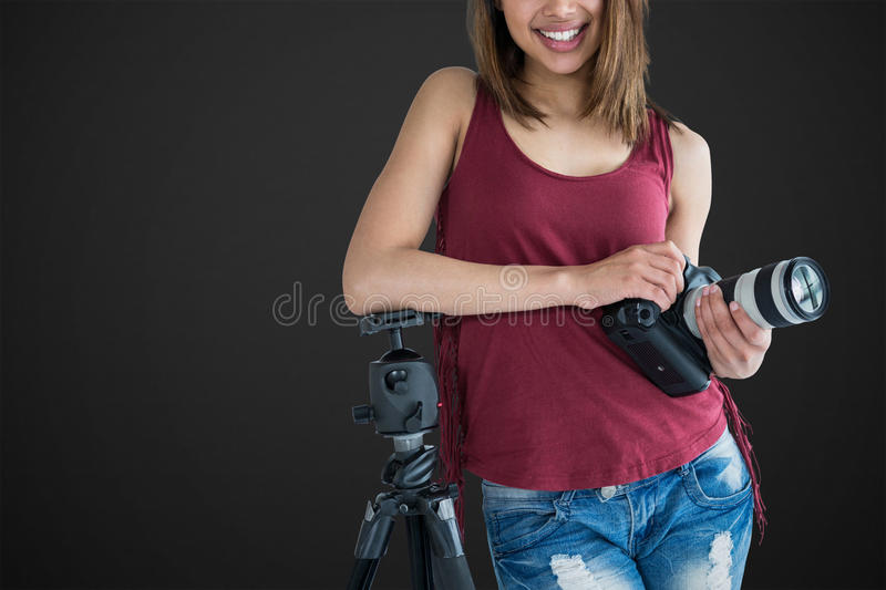 Composite image of portrait of smiling young photographer holding camera while leaning on tripod royalty free stock photos
