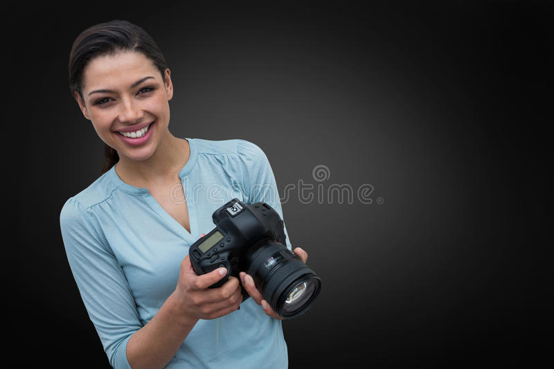 Composite image of portrait of smiling young woman holding digital camera stock photo