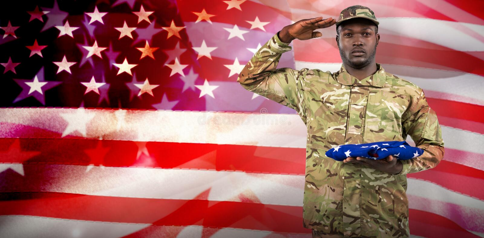 Composite image of portrait of soldier holding an american flag while stock image