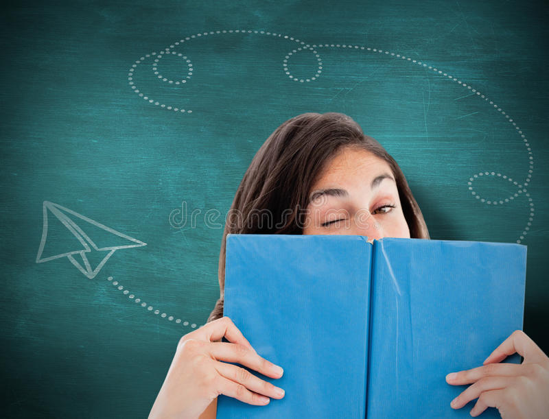 Composite image of portrait of a student winking behind a blue book stock photo
