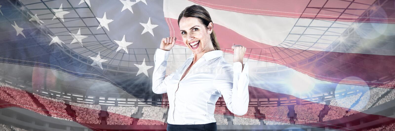 Composite image of portrait of successful businesswoman with clenched fists royalty free stock photo