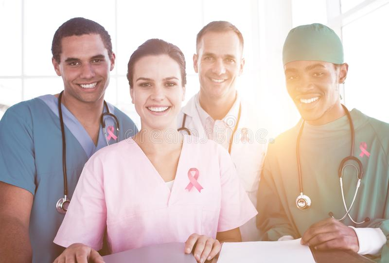 Composite image of portrait of a successful medical team at work. Portrait of a successful medical team at work against breast cancer awareness ribbon royalty free stock photography