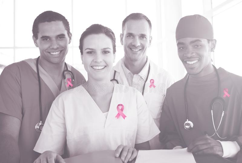 Composite image of portrait of a successful medical team at work. Portrait of a successful medical team at work against breast cancer awareness ribbon royalty free stock images