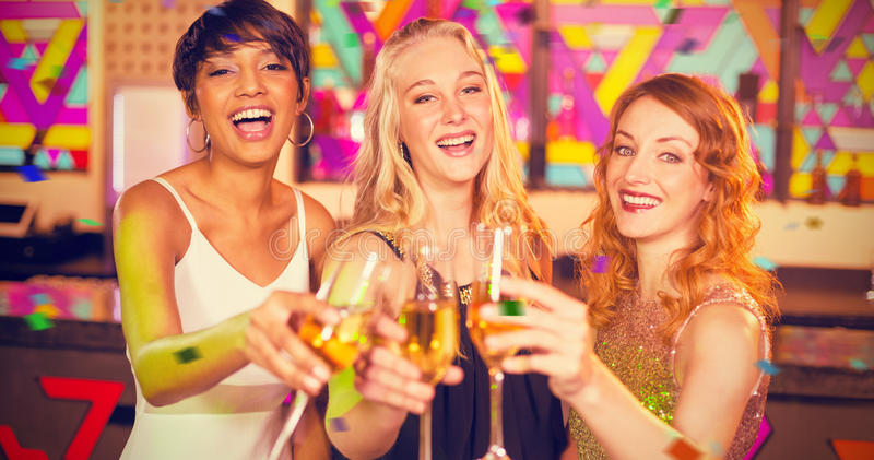Composite image of portrait of three smiling friend toasting glass of champagne royalty free stock images