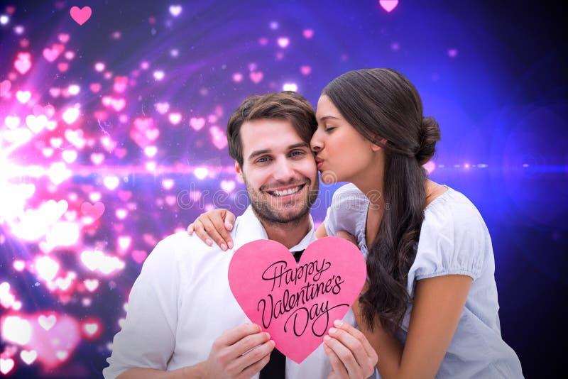 Composite image of pretty brunette giving boyfriend a kiss and her heart. Pretty brunette giving boyfriend a kiss and her heart against valentines heart design stock image