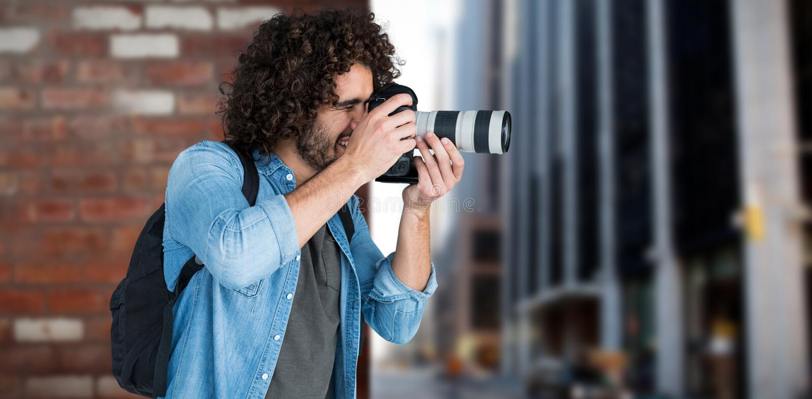Composite image of professional male photographer taking picture. Professional male photographer taking picture against wall of a house stock photos