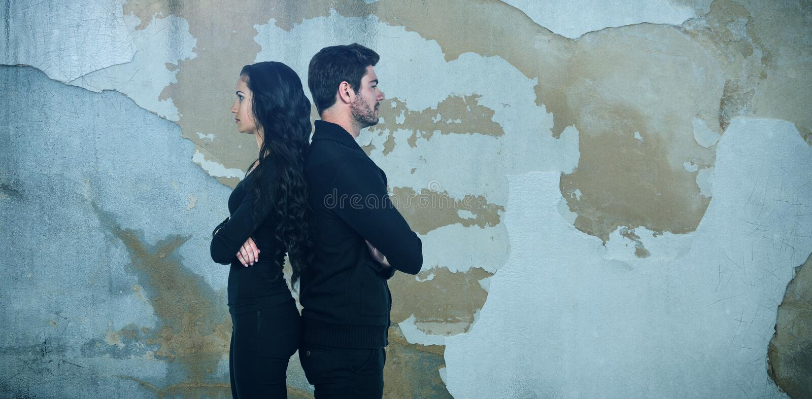 Composite image of profile view of sad couple standing back to back royalty free stock photos