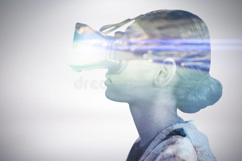 Composite image of profile view of woman wearing virtual reality glasses. Profile view of woman wearing virtual reality glasses against sunset of a beautiful day stock images