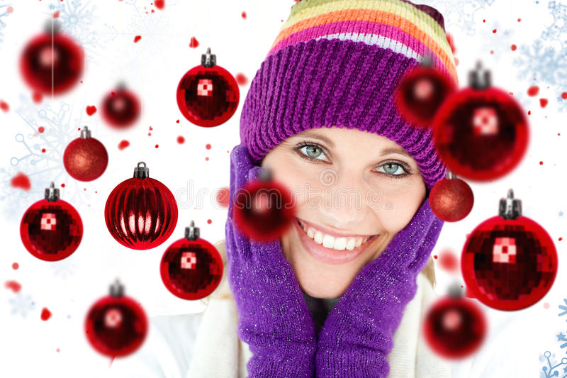 Composite image of radiant young woman with cap and gloves in the winter royalty free stock image