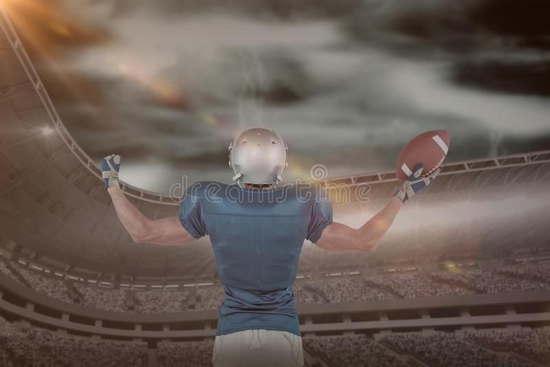 Composite image of rear view of american football player holding ball stock photography