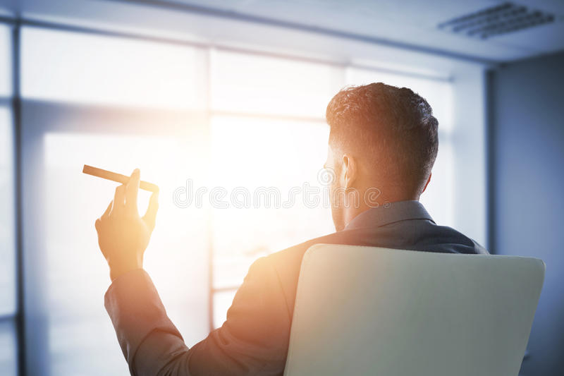 Composite image of rear view of businessman holding cigar. Rear view of businessman holding cigar against interior of modern office stock photos
