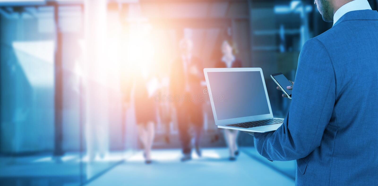 Composite image of rear view of businessman using laptop and mobile phone. Rear view of businessman using laptop and mobile phone against businesspeople walking royalty free stock photos