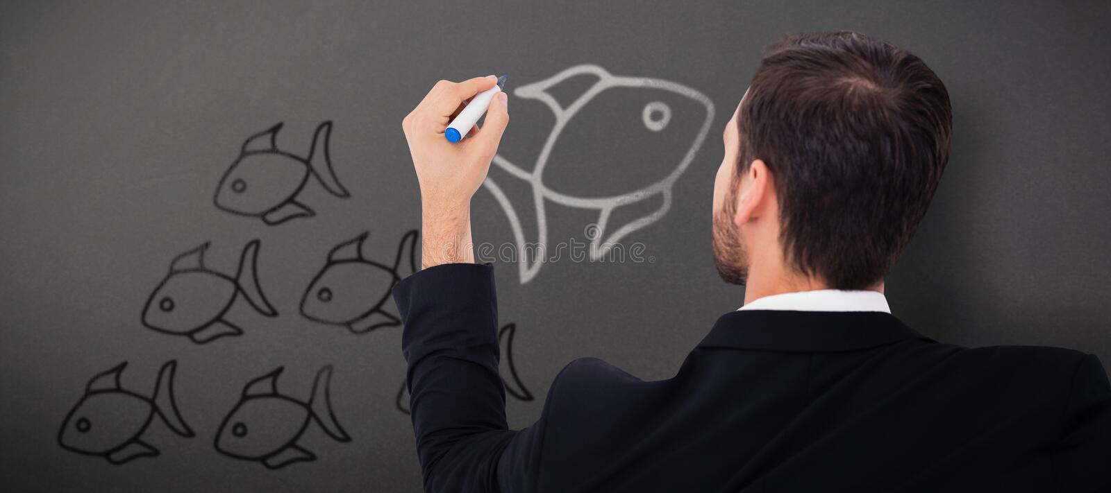 Composite image of rear view of businessman writing with marker. Rear view of businessman writing with marker against grey royalty free stock photography