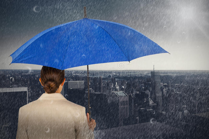 Composite image of rear view of businesswoman carrying blue umbrella. Rear view of businesswoman carrying blue umbrella against high angle view of city skyline royalty free stock photo