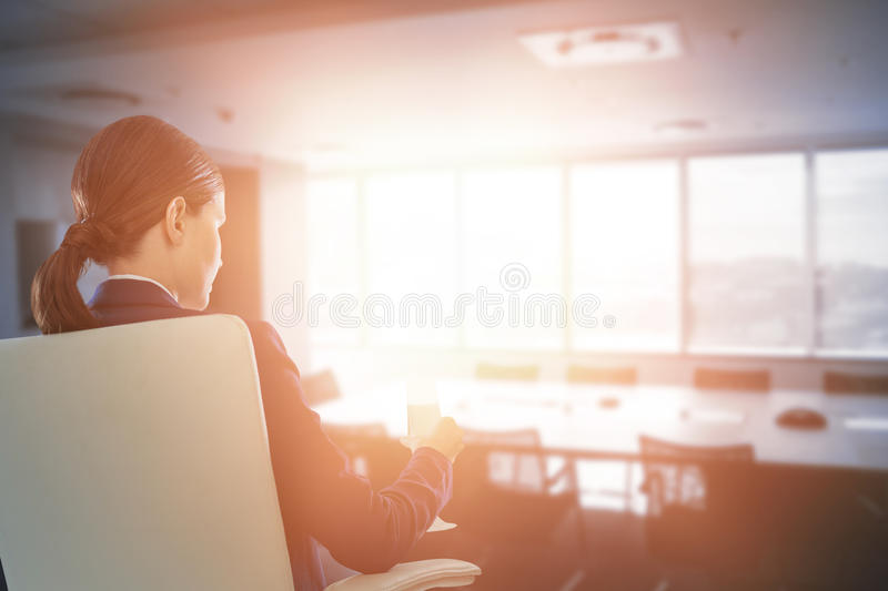 Composite image of rear view of businesswoman holding water glass while sitting on chair. Rear view of businesswoman holding water glass while sitting on chair royalty free stock photography