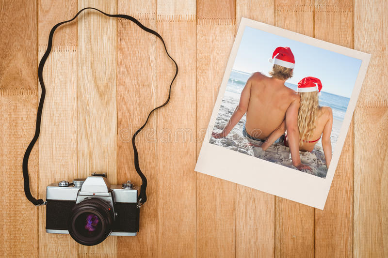 Composite image of rear view of couple sitting on beach. Rear view of couple sitting on beach against view of an old camera stock image