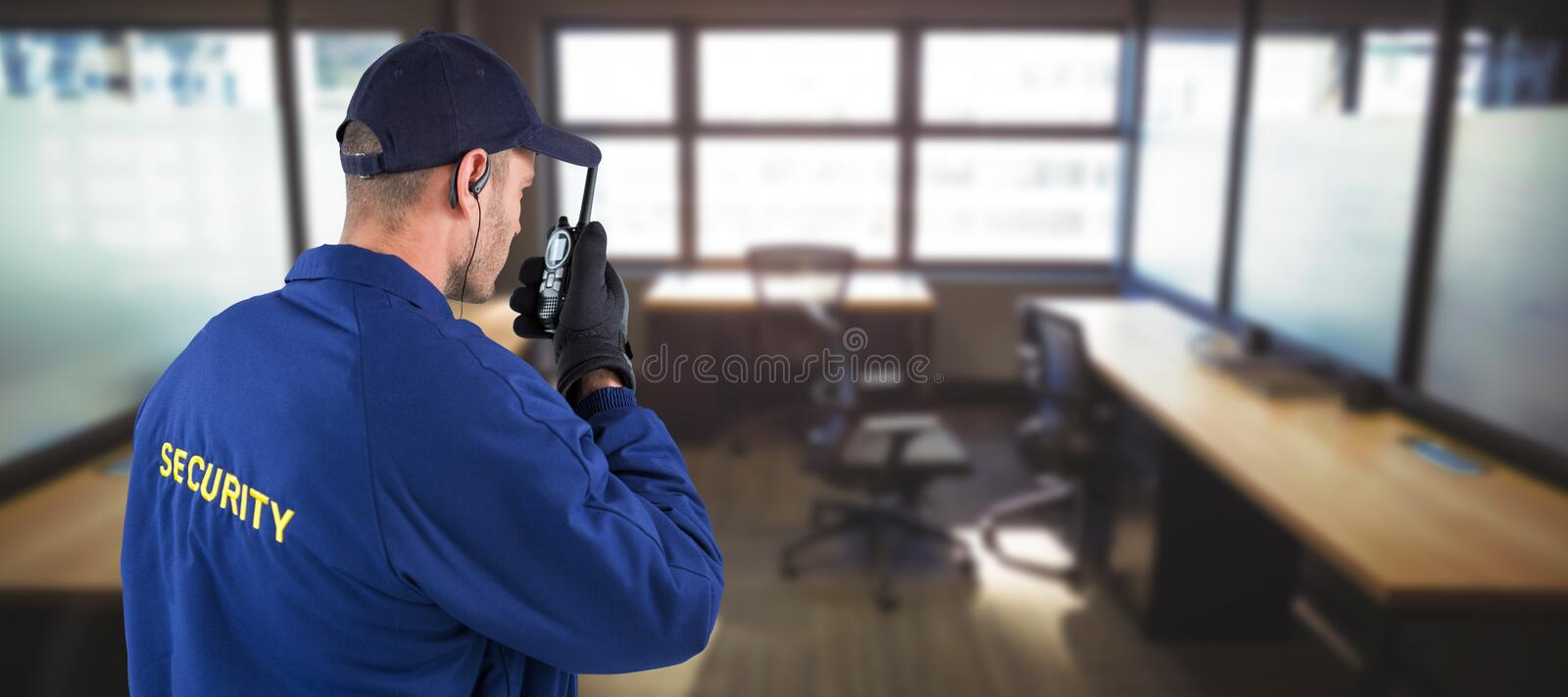 Composite image of rear view of focused security officer talking on walkie talkie. Rear view of focused security officer talking on walkie talkie against table royalty free stock photos