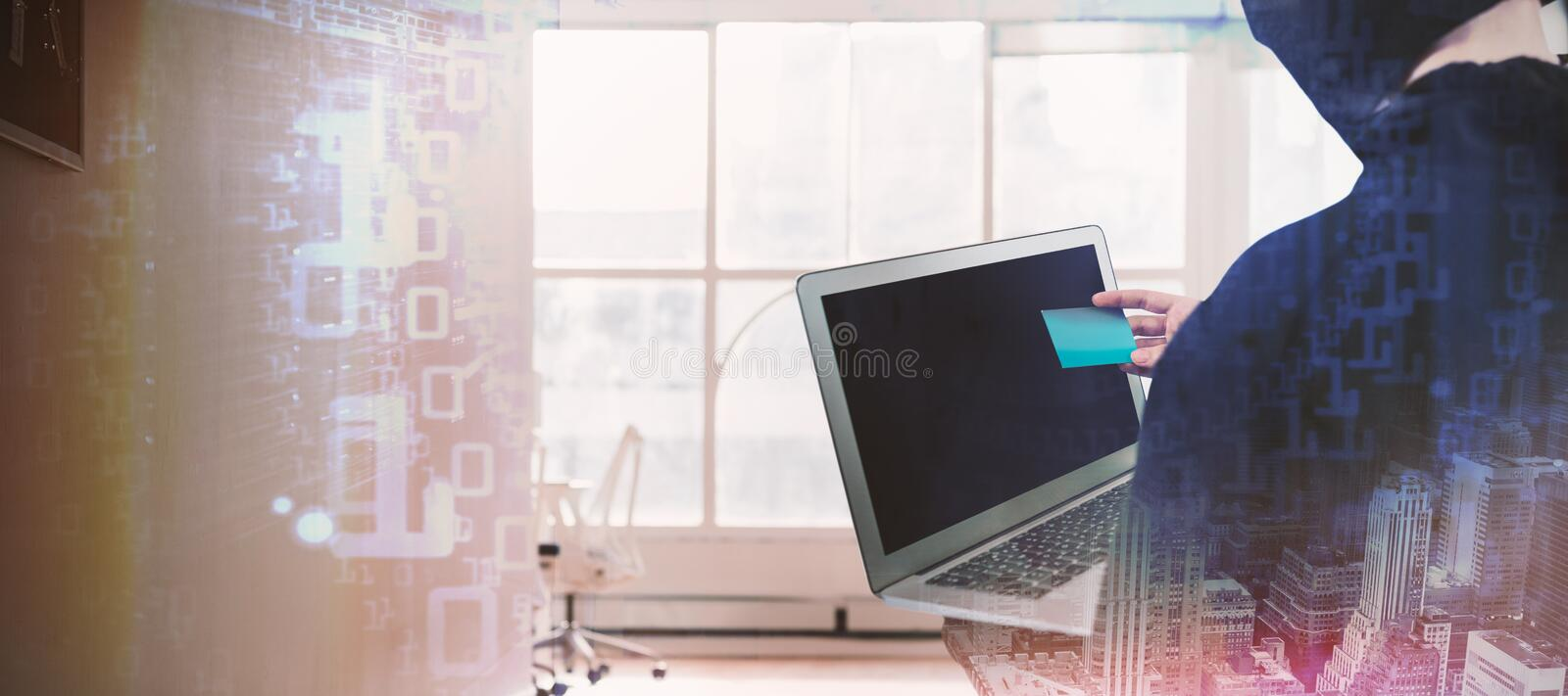 Composite image of rear view of hacker using laptop and credit card royalty free stock photography