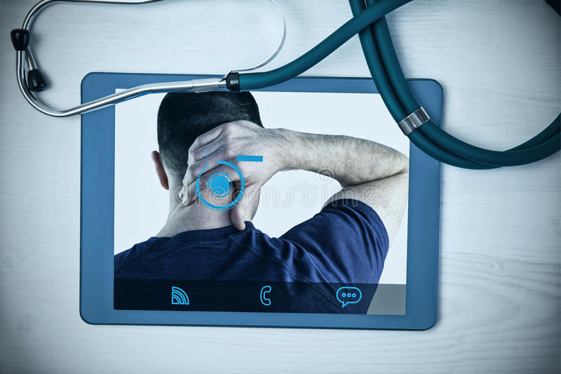 Composite image of rear view of a man with neck pain. Rear view of a man with neck pain against tablet and stethoscope on desk stock photos