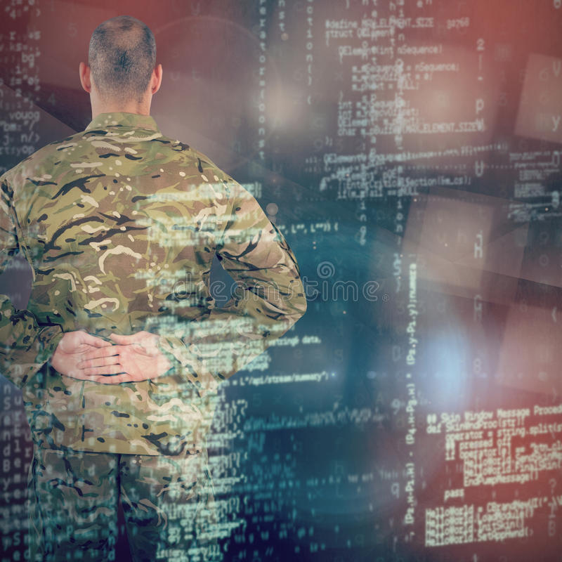 Composite image of rear view of soldier standing with his hands behind back. Rear view of soldier standing with his hands behind back against abstract black room royalty free stock photo