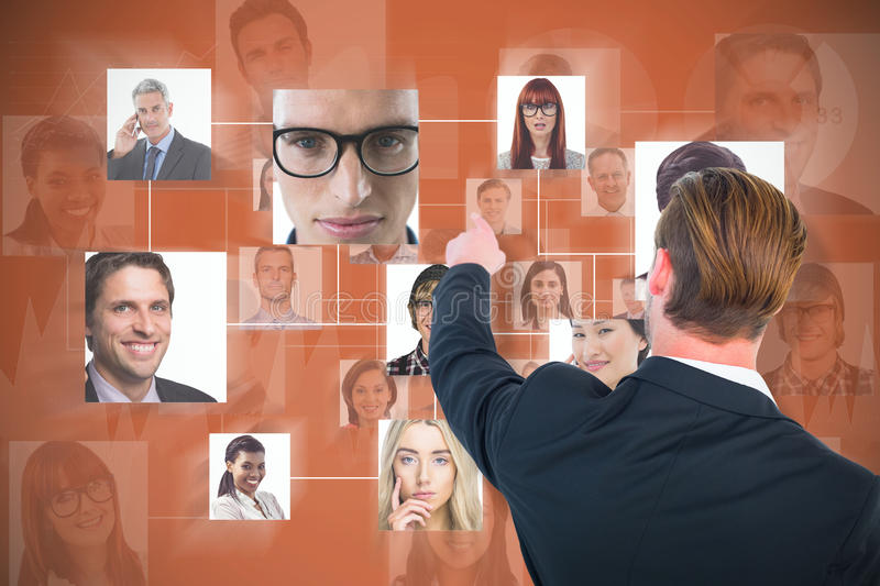 Composite image of rear view of young businessman in suit pointing royalty free stock photo