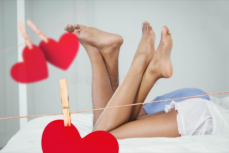Composite image of red hanging hearts and couple lying on bed with crossed leg stock photography