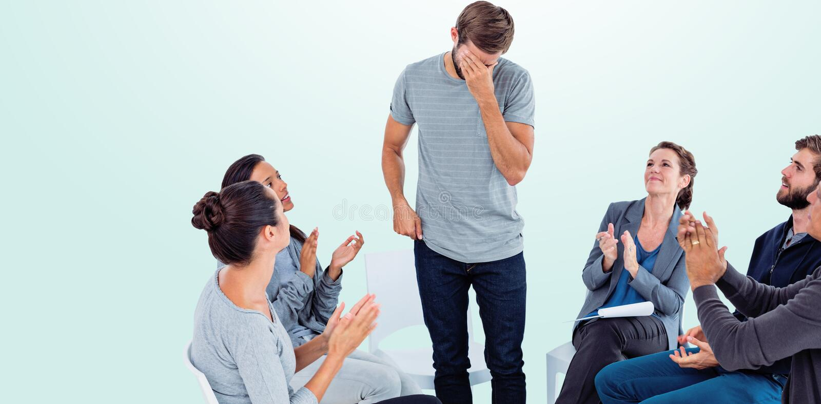 Composite image of rehab group applauding delighted man standing up. Rehab group applauding delighted men standing up against blue background stock images