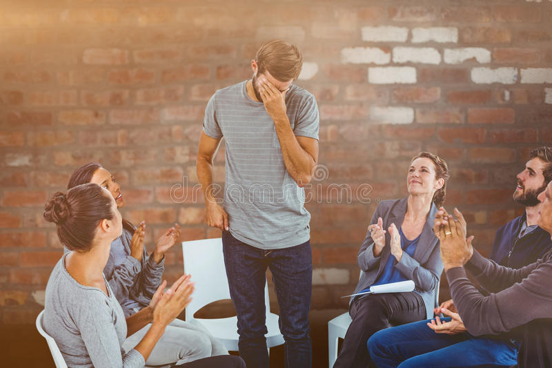 Composite image of rehab group applauding delighted man standing up. Rehab group applauding delighted men standing up against brick wall royalty free stock images