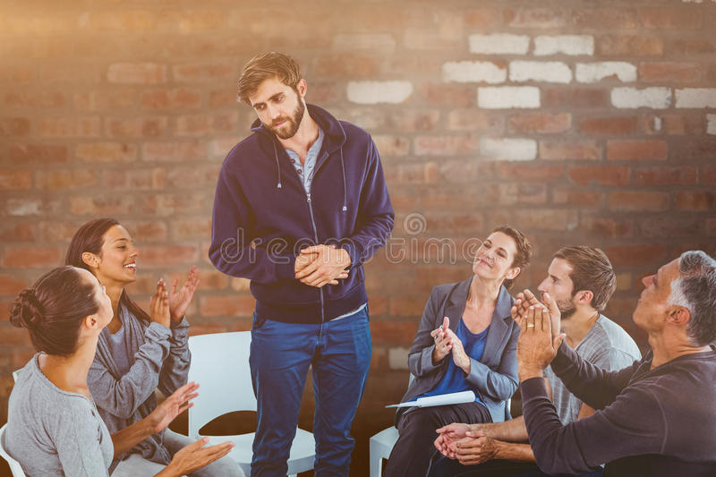 Composite image of rehab group applauding delighted man standing up. Rehab group applauding delighted men standing up against brick wall royalty free stock image