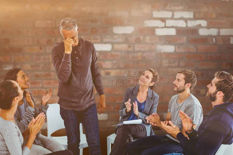 Composite image of rehab group applauding delighted man standing up. Rehab group applauding delighted men standing up against brick wall royalty free stock photos
