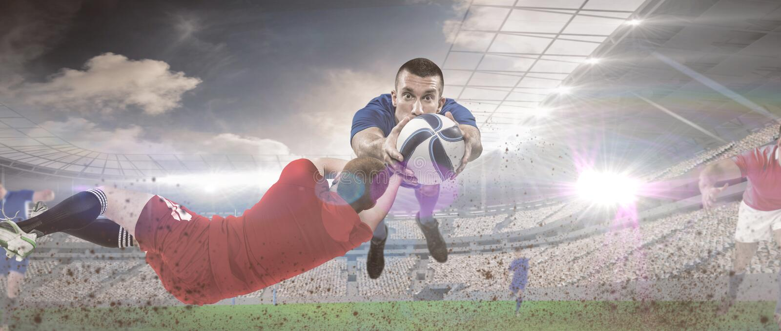 Composite image of a rugby player scoring a try. A rugby player scoring a try against rugby match royalty free stock image