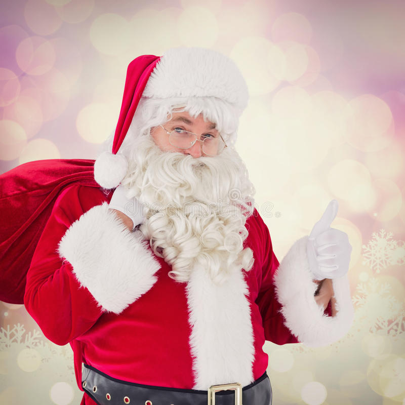 Composite image of santa claus with his sack and thumbs up stock photography
